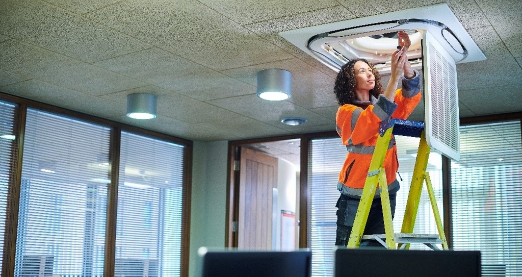 Maintenance worker on a ladder in conference room changing an Azure IoT sensor in a lighting fixture.
